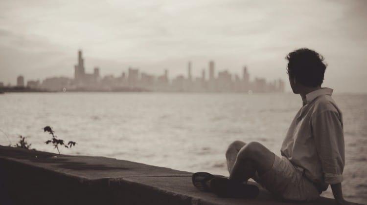 Man sitting by New York City view bay