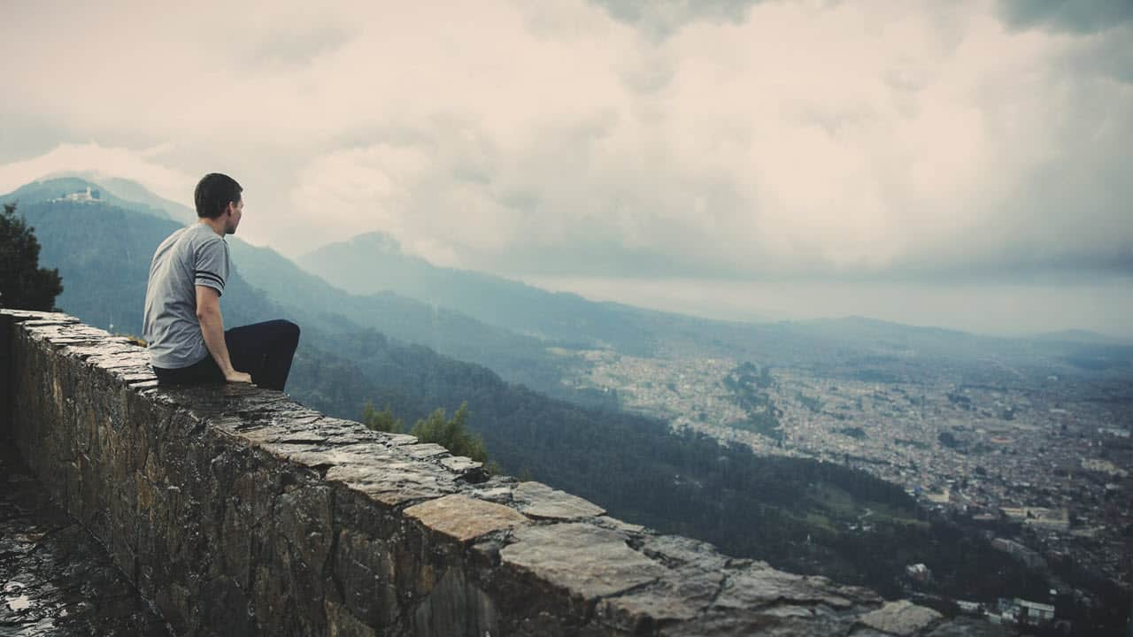 Young Man Sitting on Stone Wall - PersonalProfitability.com